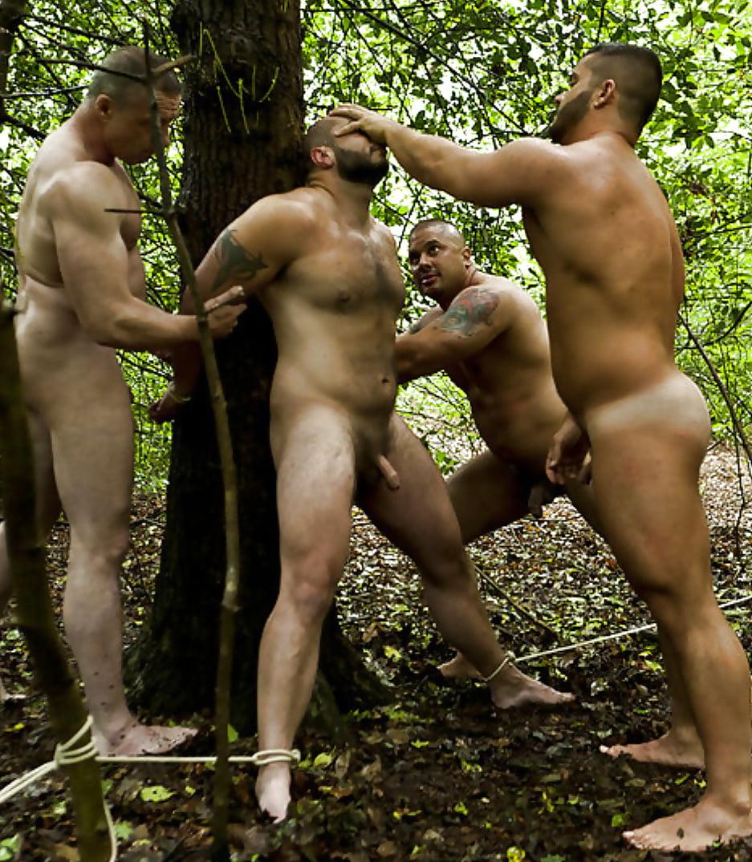 Naked man lying on root tree stock photo