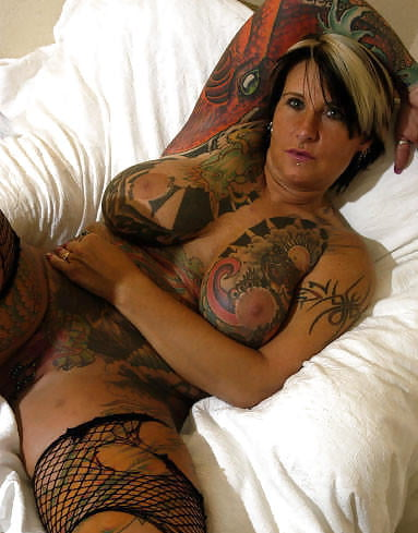 Tattooed milf with pierced navel is fucked by a black monster on the sofa