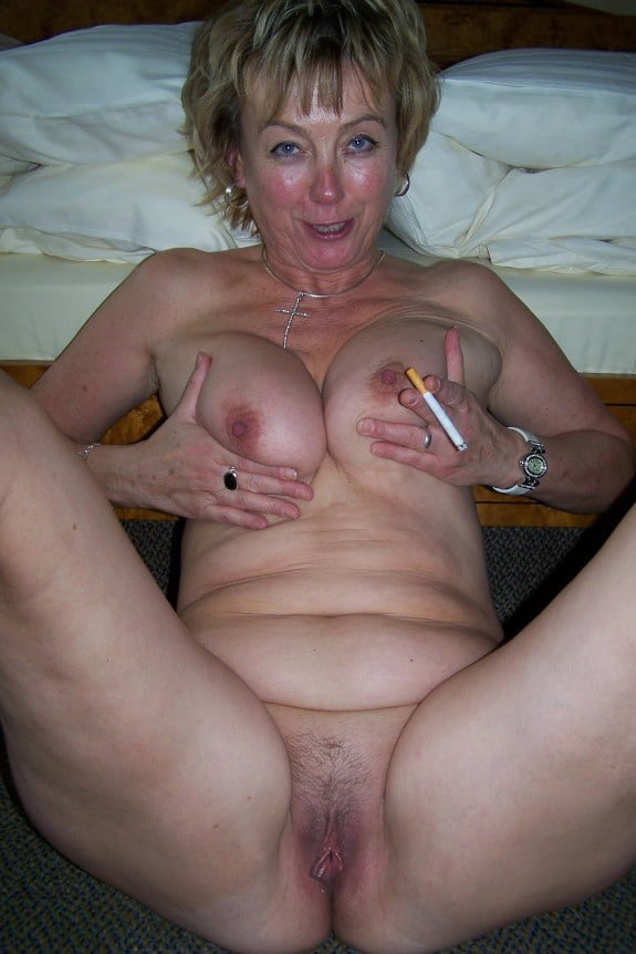 Mature woman in a bikini using the smoking area to smoke a cigarette stock photo