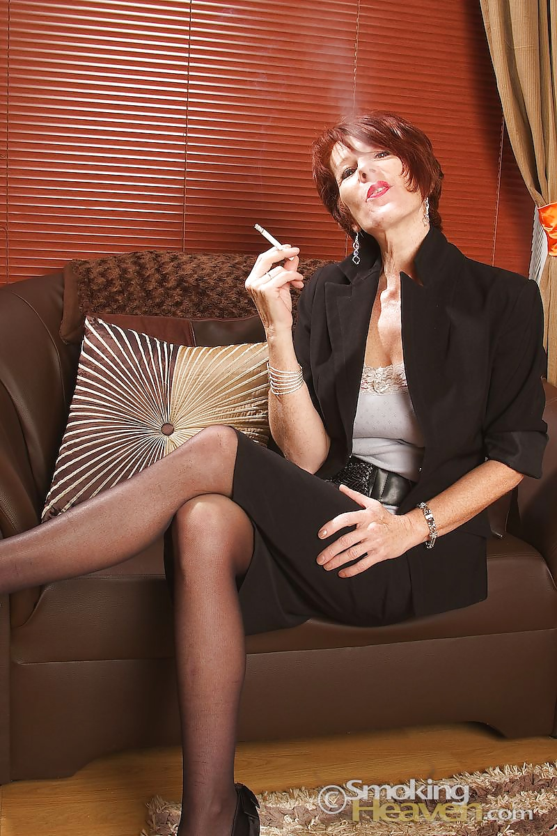 Young brunette woman smoking cigarette while sitting on bed against of